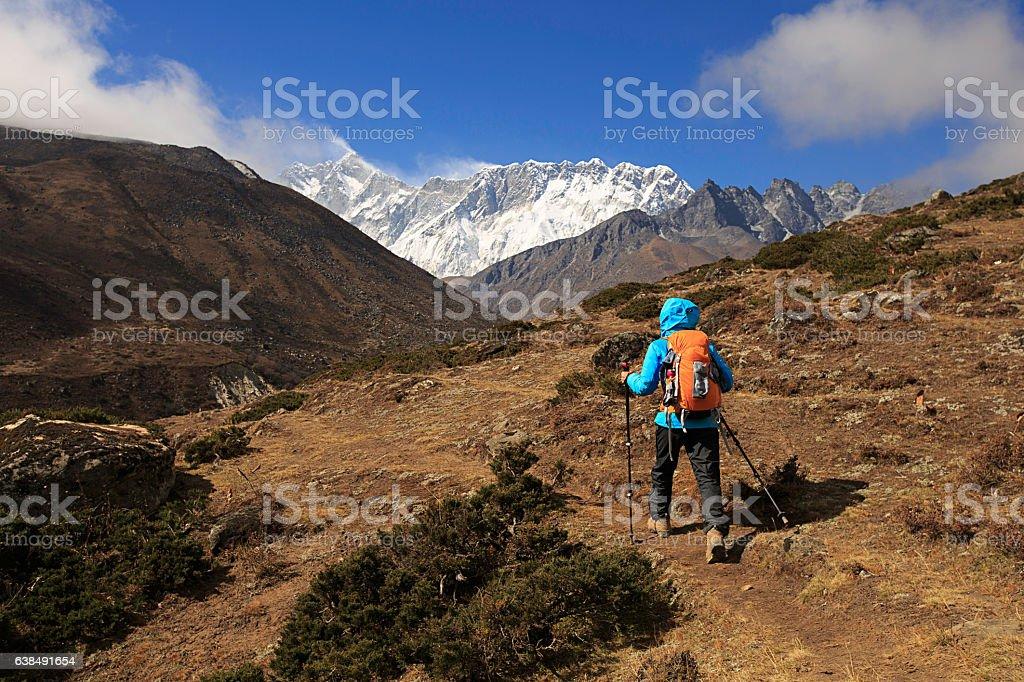 young woman backpacker trekking on himalaya mountains, stock photo