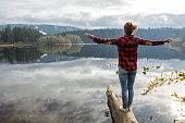 Young woman balances on a tree log above the lake