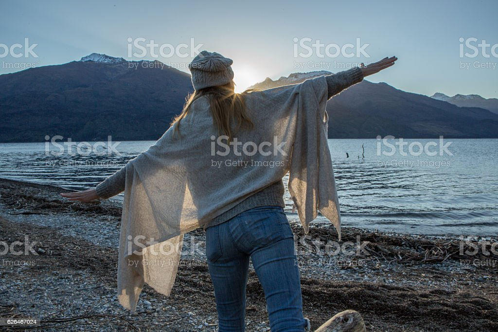 Young woman balances on a tree log above the lake stock photo