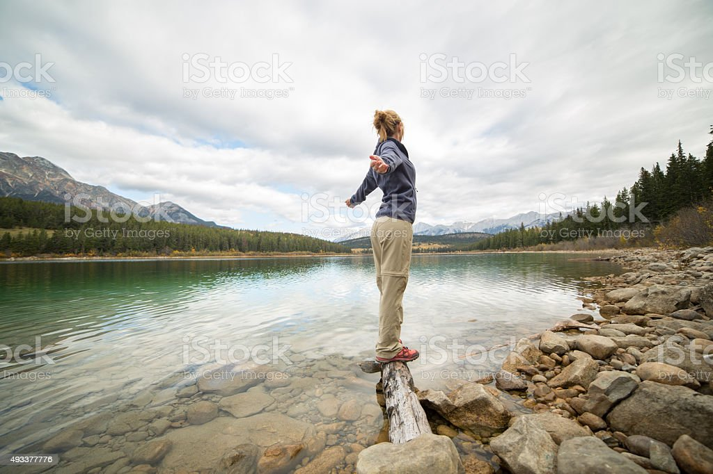 Young woman balances on log above lake arms outstretched stock photo