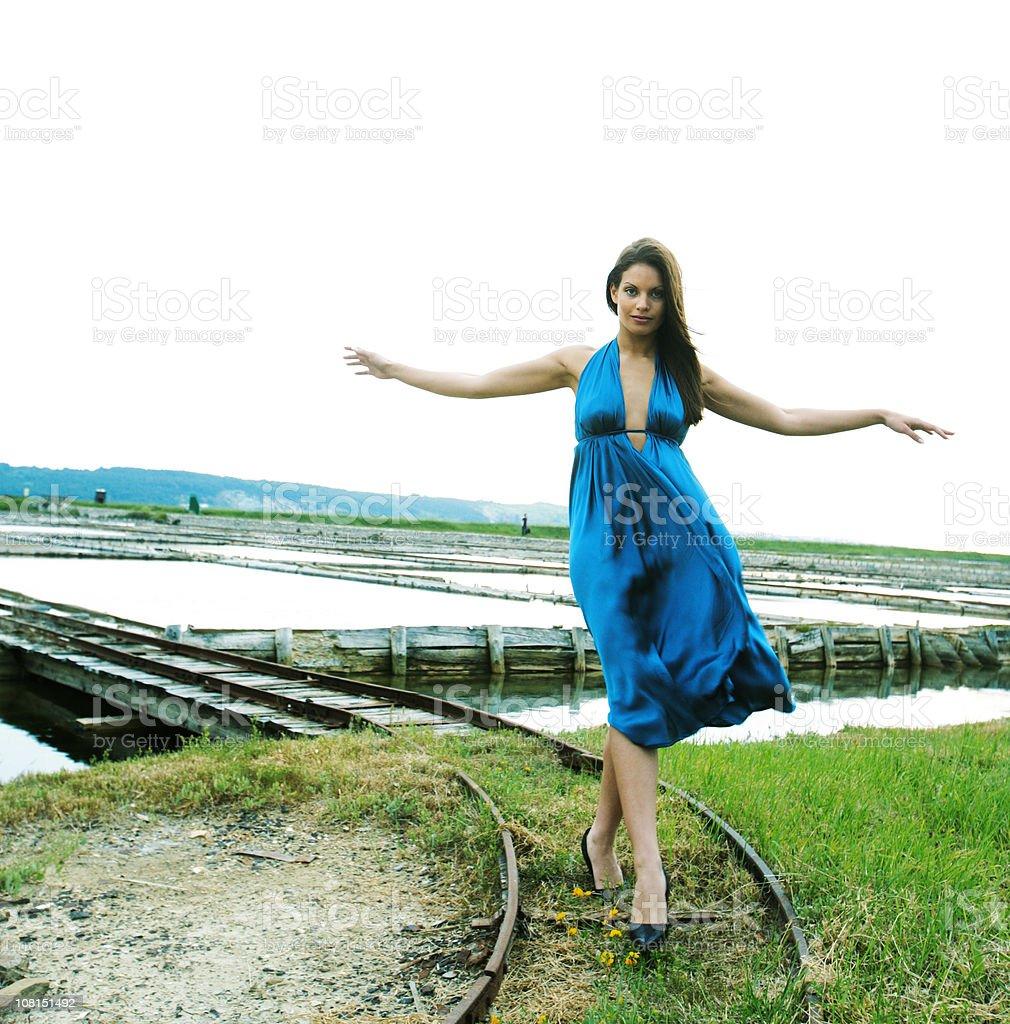 Young Woman Balancing and Walking on Railway Tracks royalty-free stock photo