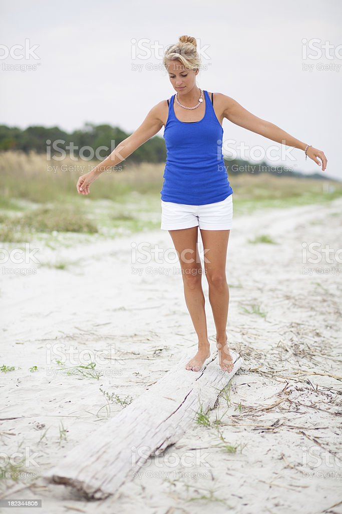 Young woman balancing on drift wood royalty-free stock photo