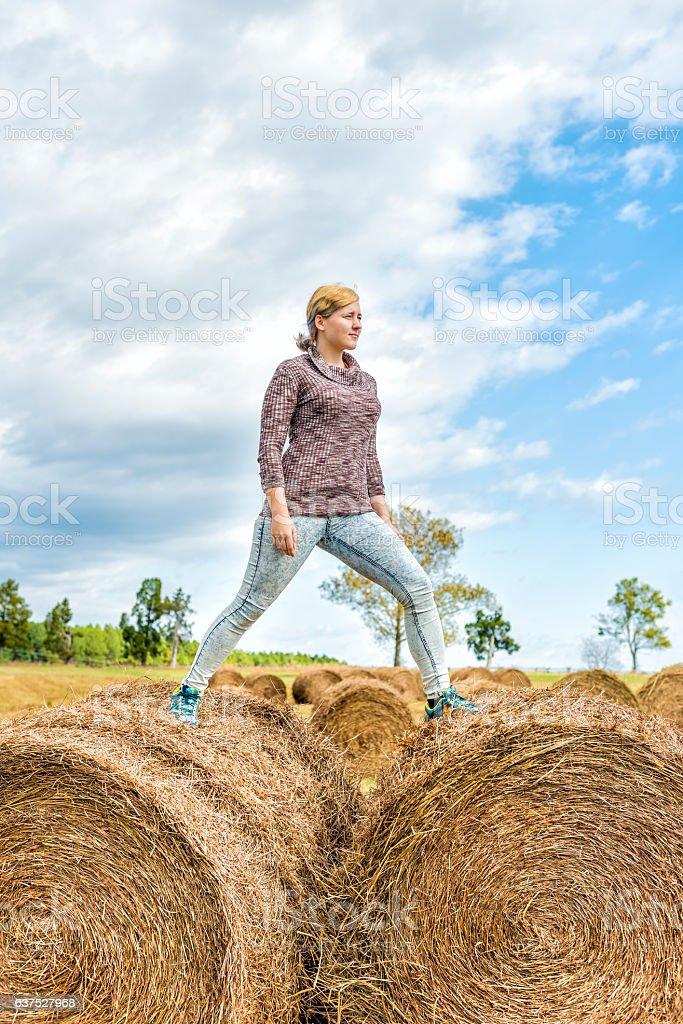 Young woman balancing on hay roll bales stock photo