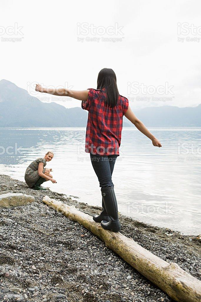 Young woman balancing on log royalty-free stock photo