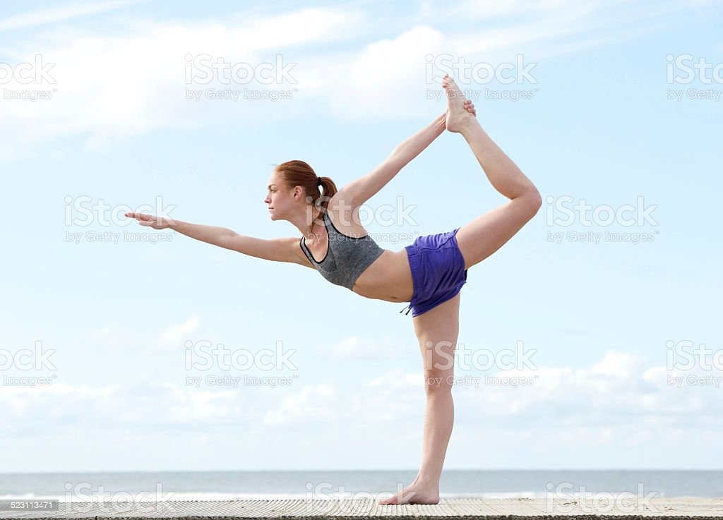 Young woman balancing on one leg in yoga position stock photo