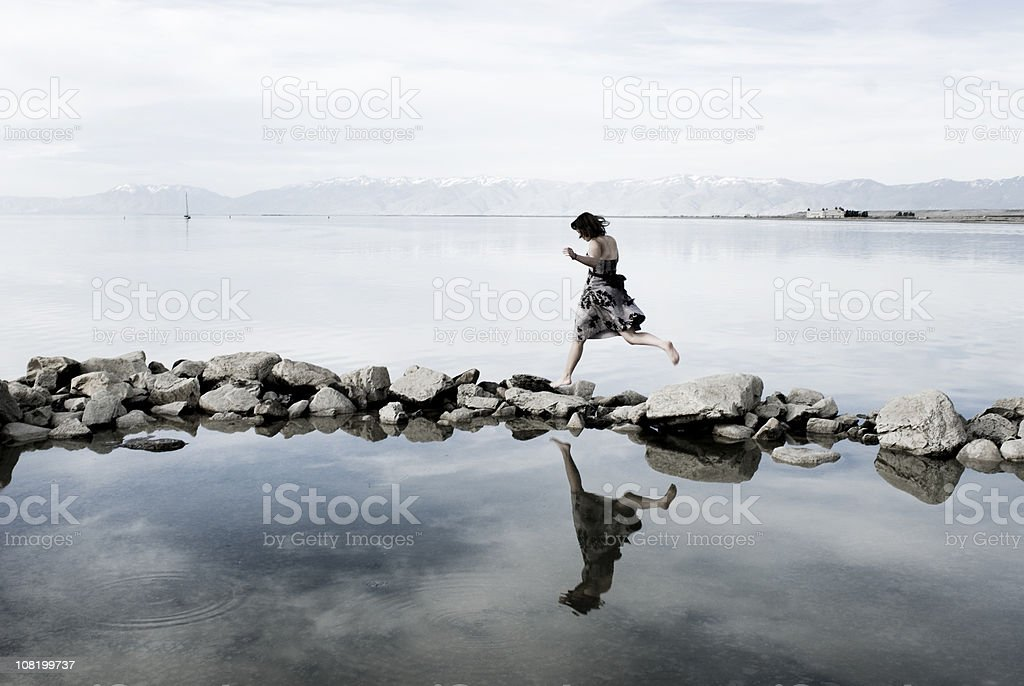 Young Woman Balancing on Rocks in Lake royalty-free stock photo