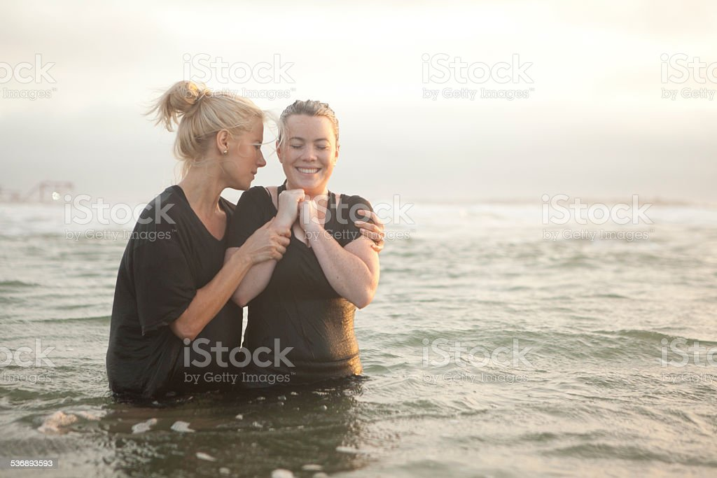 Young woman baptized in the ocean stock photo