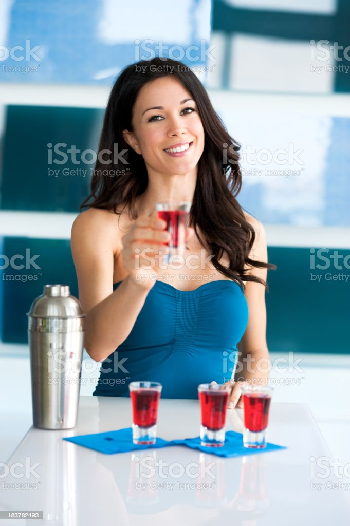 Young Woman Bartender Holding Red Shot of Liquor royalty-free stock photo