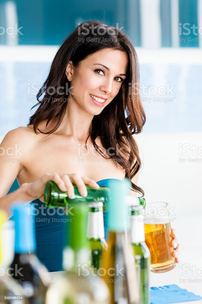 Young Woman Bartender Pouring Beer into Glass stock photo