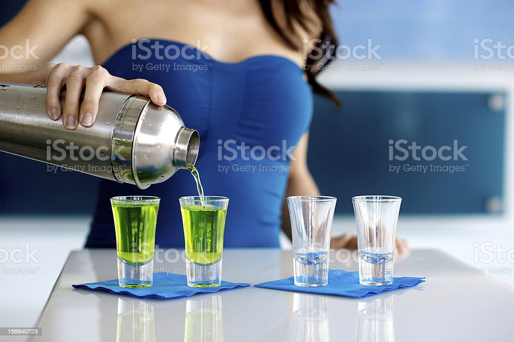Young Woman Bartender Pouring Green Shot of Liquor royalty-free stock photo
