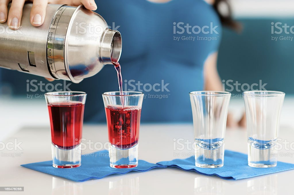 Young Woman Bartender Pouring Red Shot of Liquor royalty-free stock photo