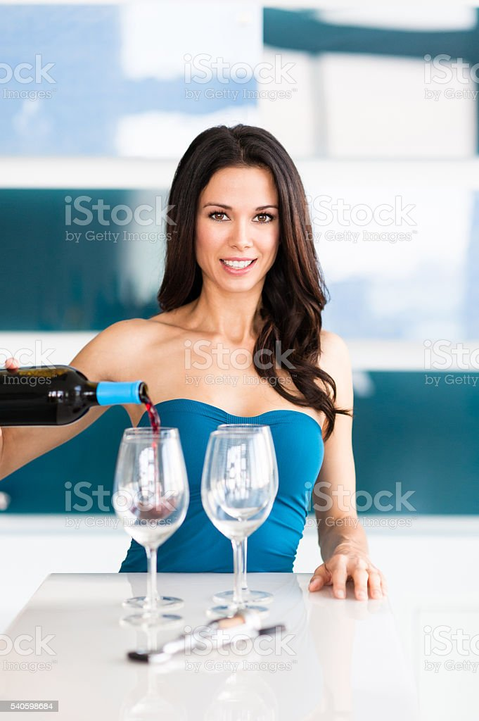 Young Woman Bartender Pouring Wine Bottle stock photo