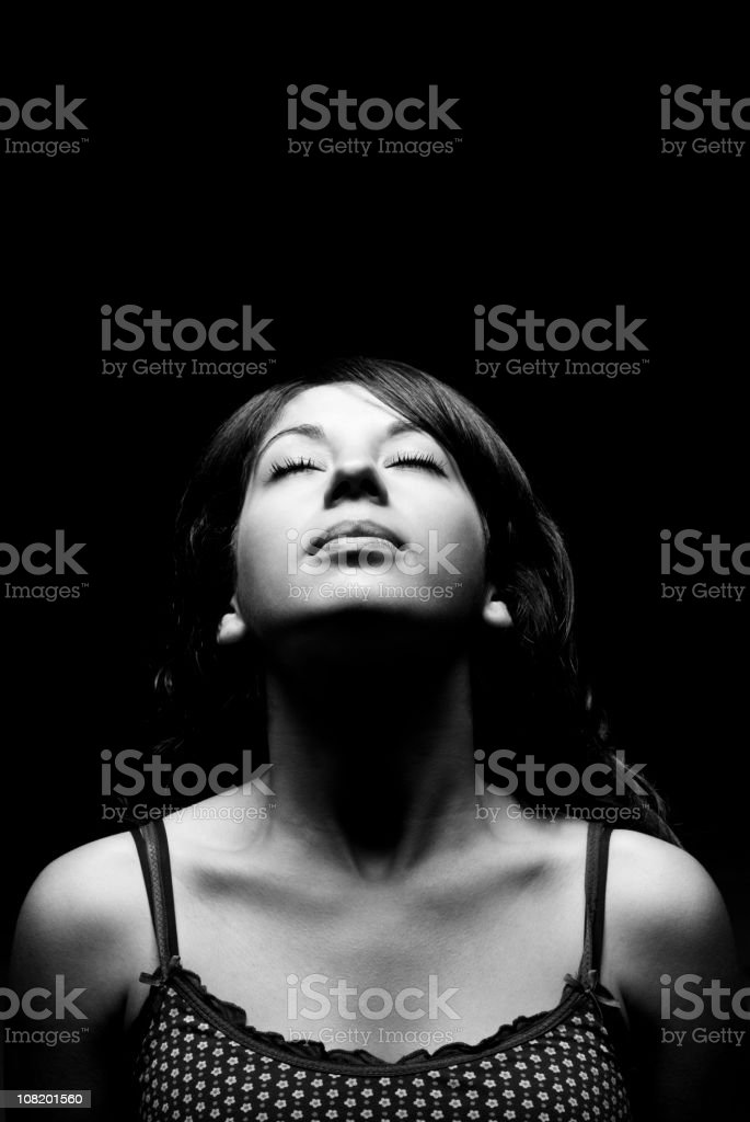 Young Woman Basking in Light Hitting Her Face stock photo