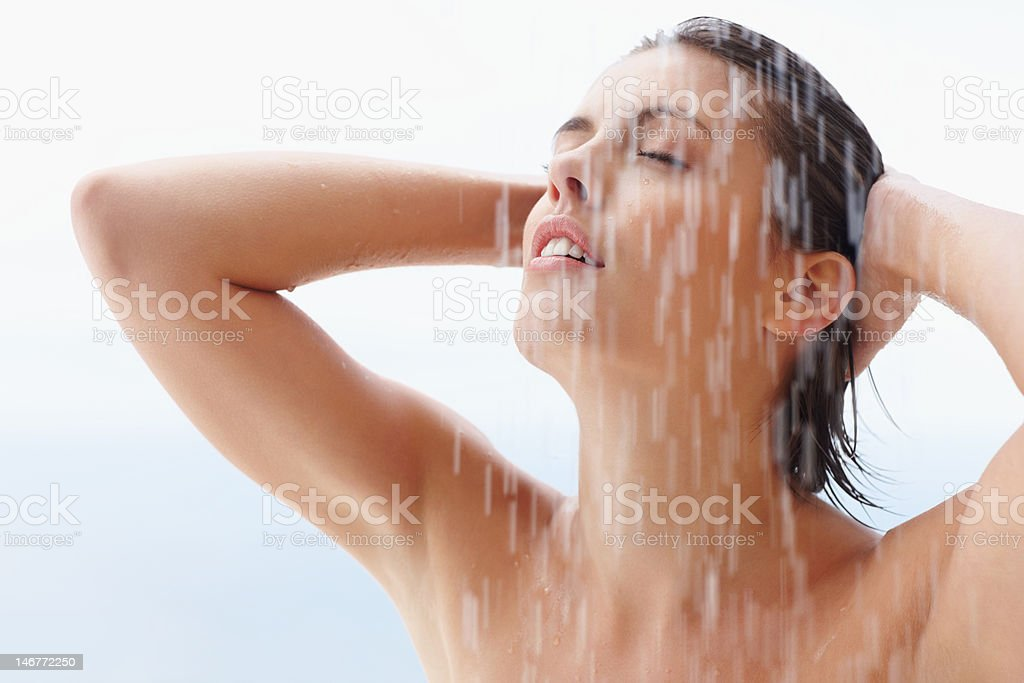 Young woman bathing under an outdoor shower royalty-free stock photo