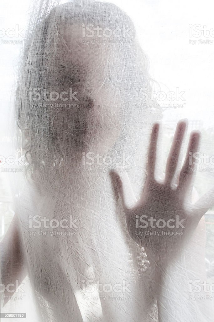 Young Woman Behind a White Curtain stock photo