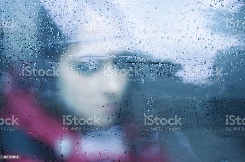 Young woman behind a window, after the rain stock photo