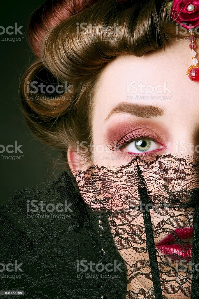 Young Woman Behind Lace Fan stock photo