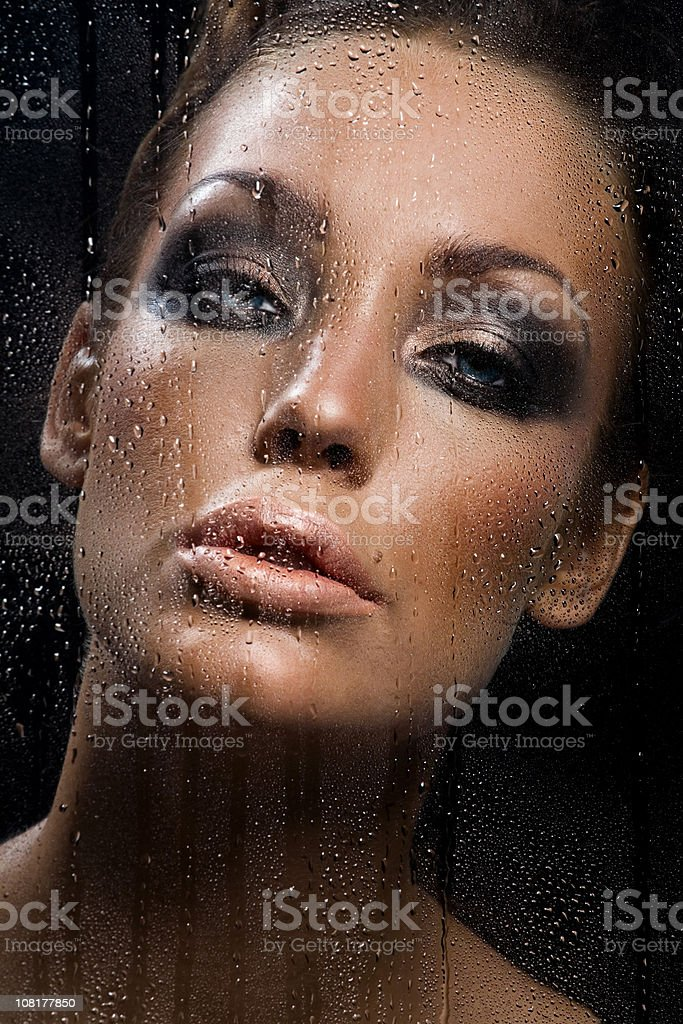 Young Woman Behind Wet Window royalty-free stock photo
