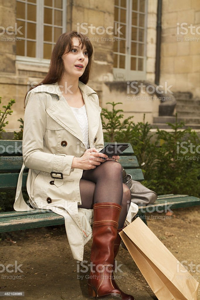 Young woman, bench in a park, reading kindle royalty-free stock photo
