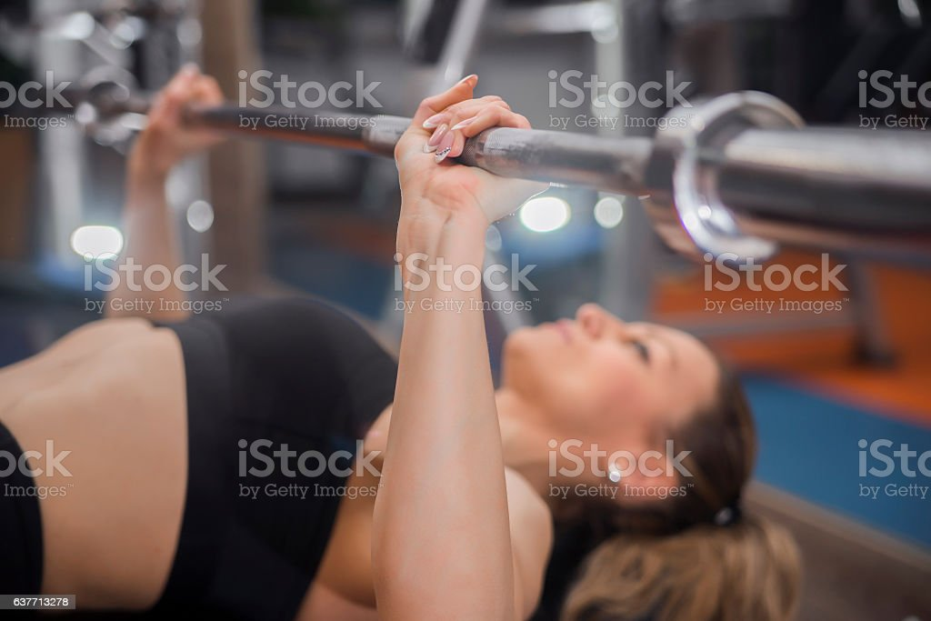 Young woman bench pressing weights at gym stock photo