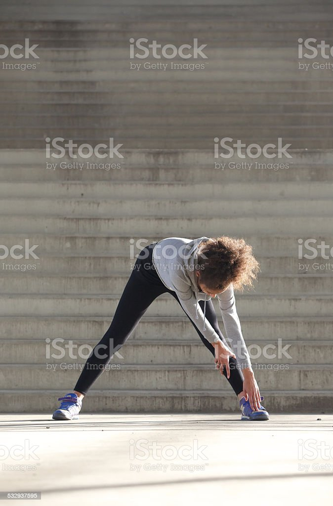 Young woman bending down stretching leg muscles stock photo