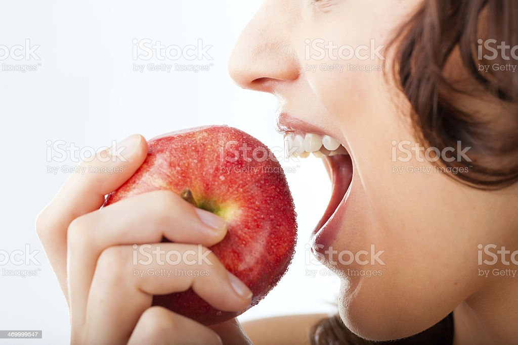 Young woman bites in a apple stock photo
