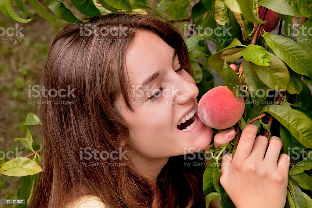 Young woman bites into peach stock photo