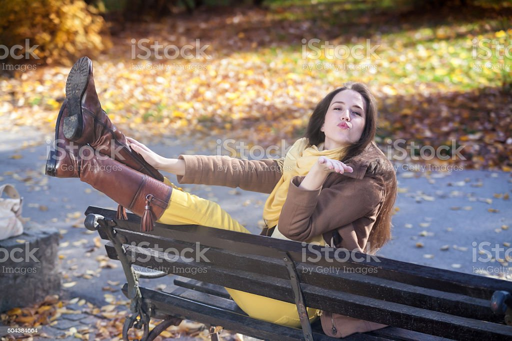 Young woman blowing a kiss in park. stock photo