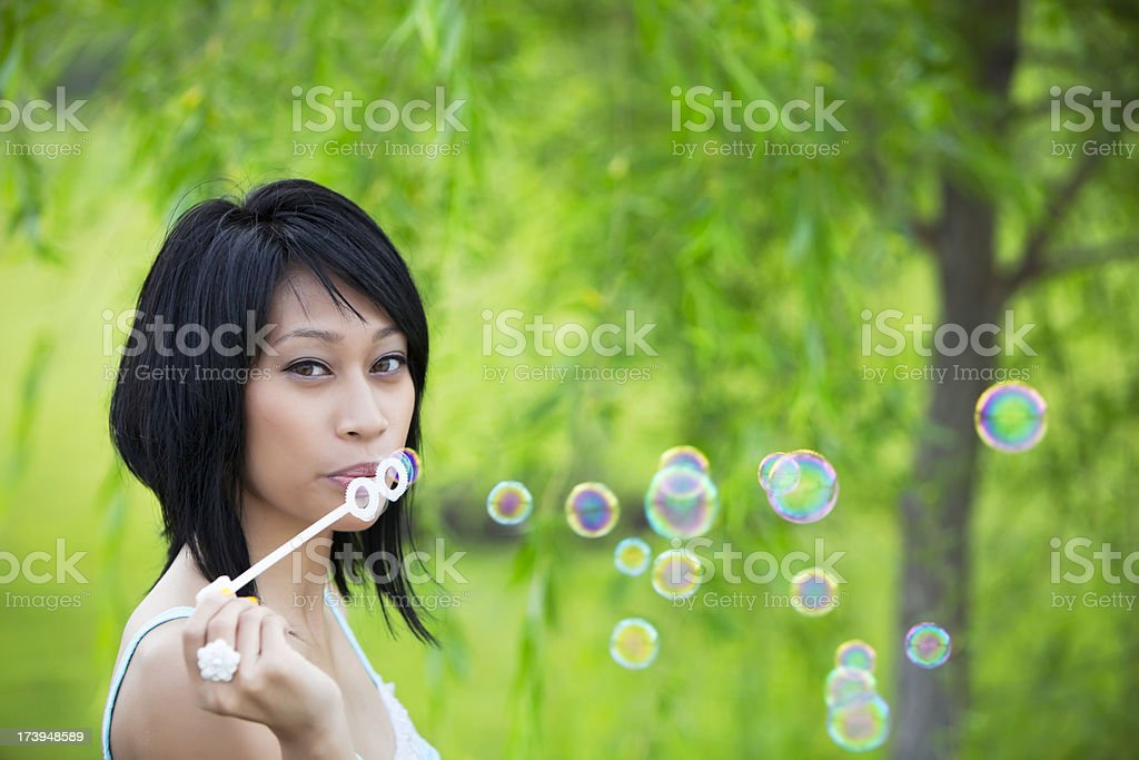 Young woman blowing bubbles in a park royalty-free stock photo