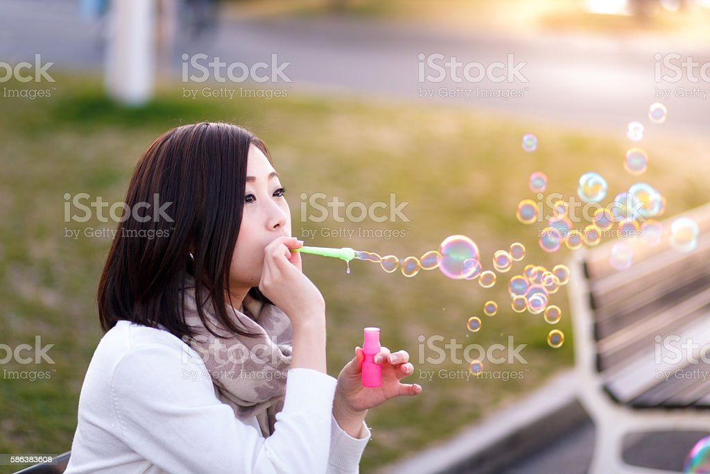 Young woman blowing bubbles in park stock photo
