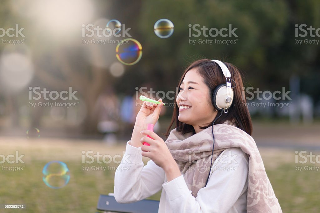 Young woman blowing bubbles in park with happiness stock photo
