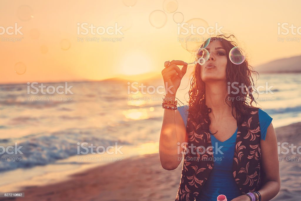 Young woman blowing bubbles on the beach stock photo