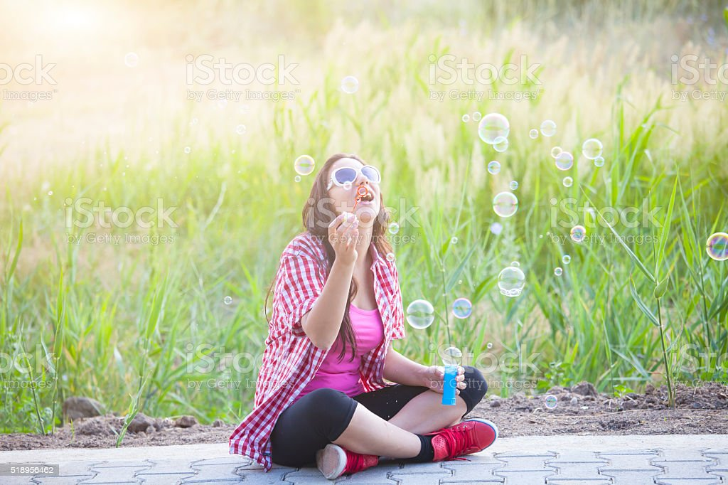 Young woman blowing bubbles outdoor stock photo