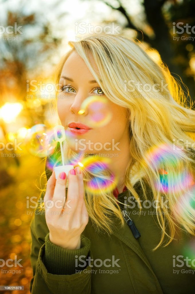Young Woman Blowing Bubbles Outside in Autumn royalty-free stock photo