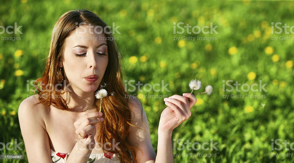 Young woman blowing dandelion royalty-free stock photo