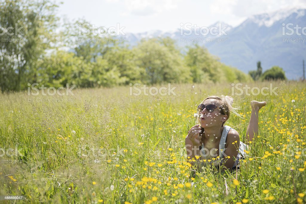 Young woman blowing flower stock photo
