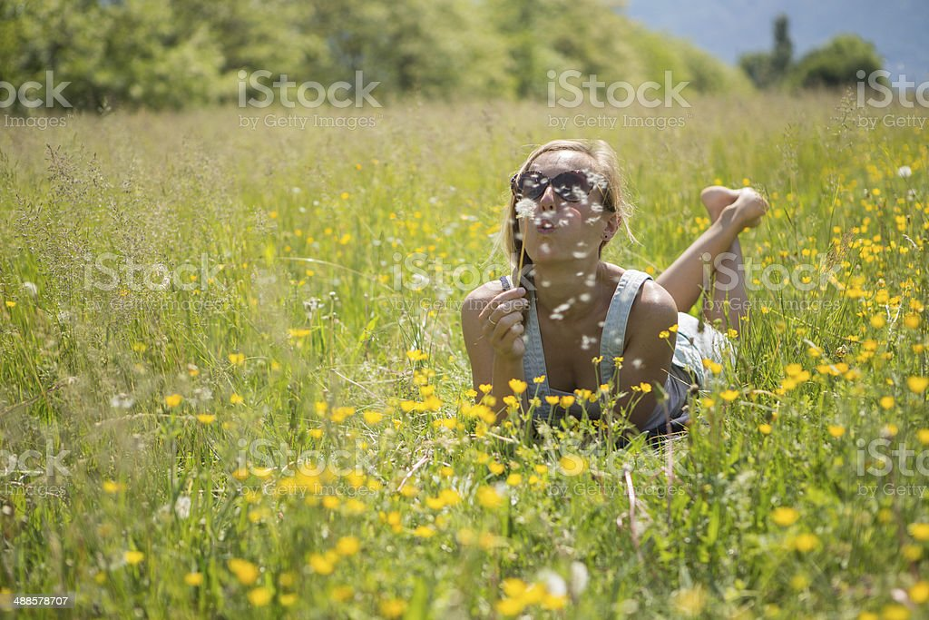 Young woman blowing flowers in the field stock photo
