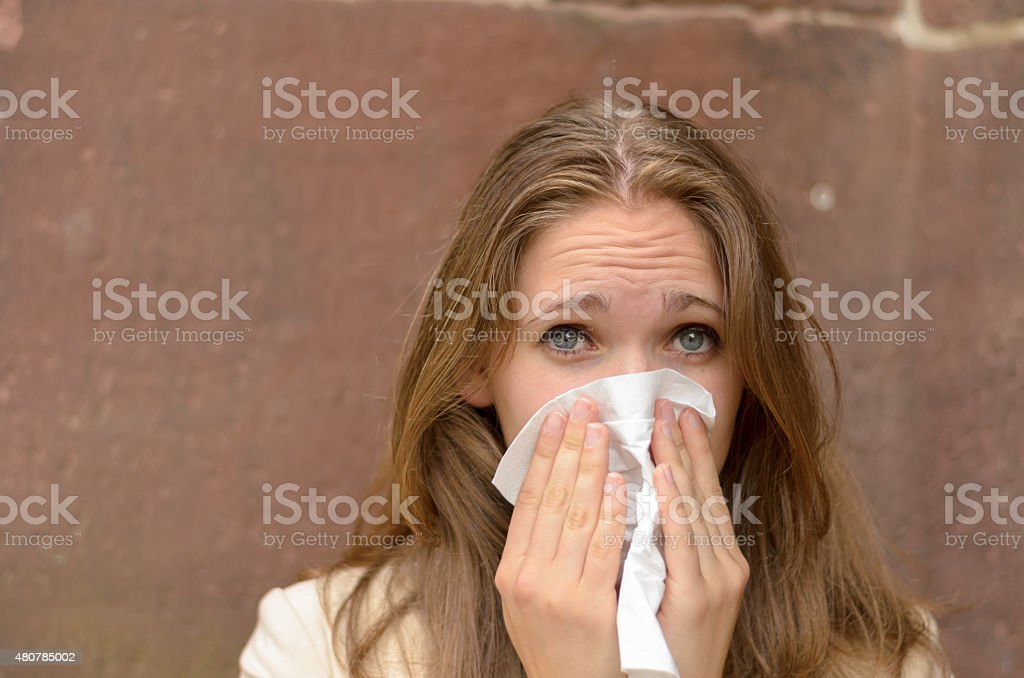 Young woman blowing her nose on a handkerchief stock photo
