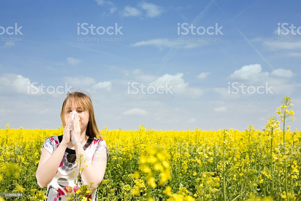 Young woman blowing her nose on the rape field royalty-free stock photo