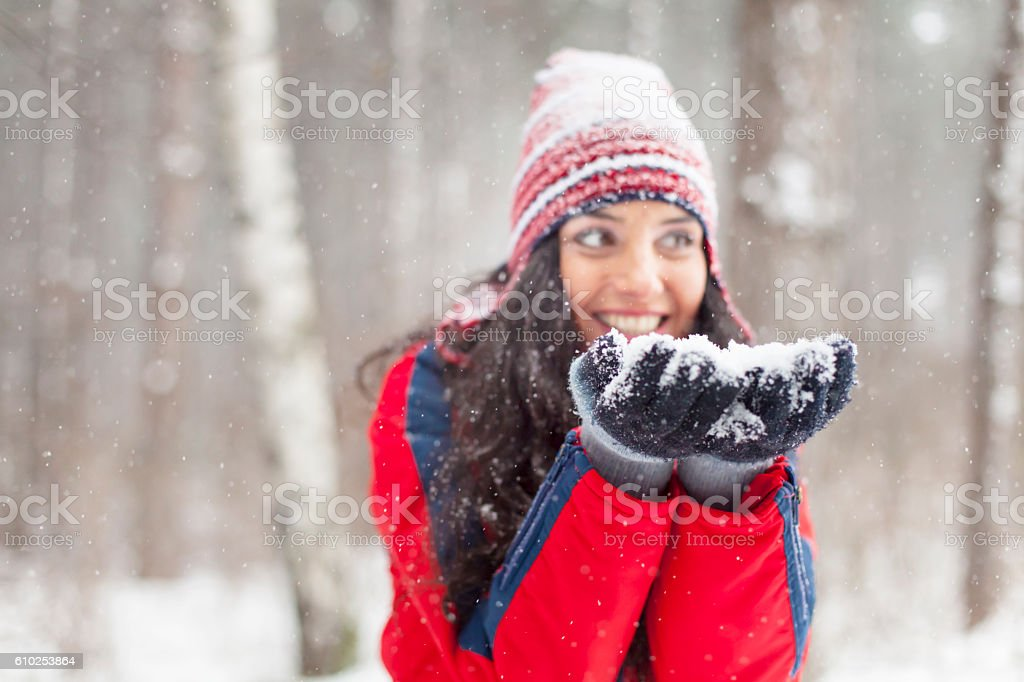 Young woman blowing snow in the snow forest stock photo