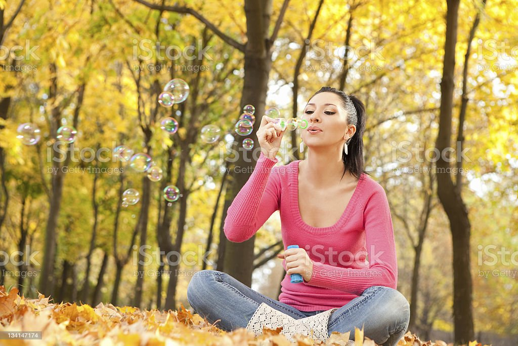 Young woman blowing soap bubble in the autumn park royalty-free stock photo