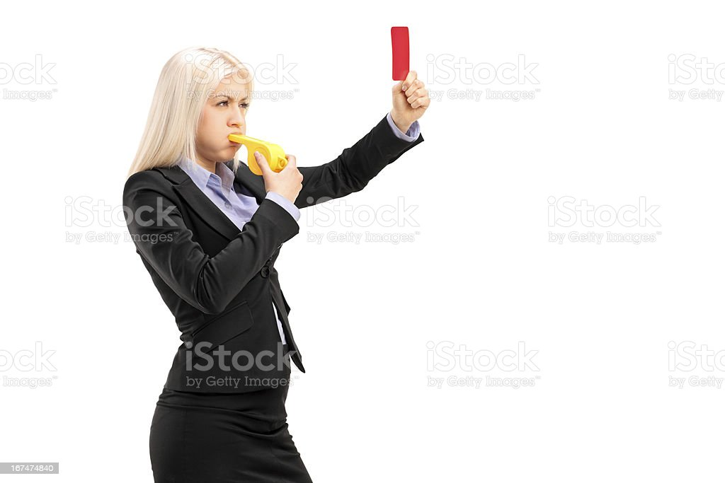 Young woman blowing whistle and showing a red card royalty-free stock photo