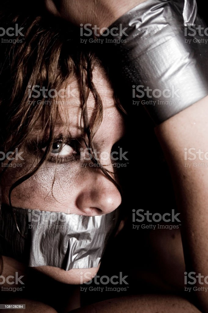 Young Woman Bound with Duct Tape and Make-Up Everywhere stock photo