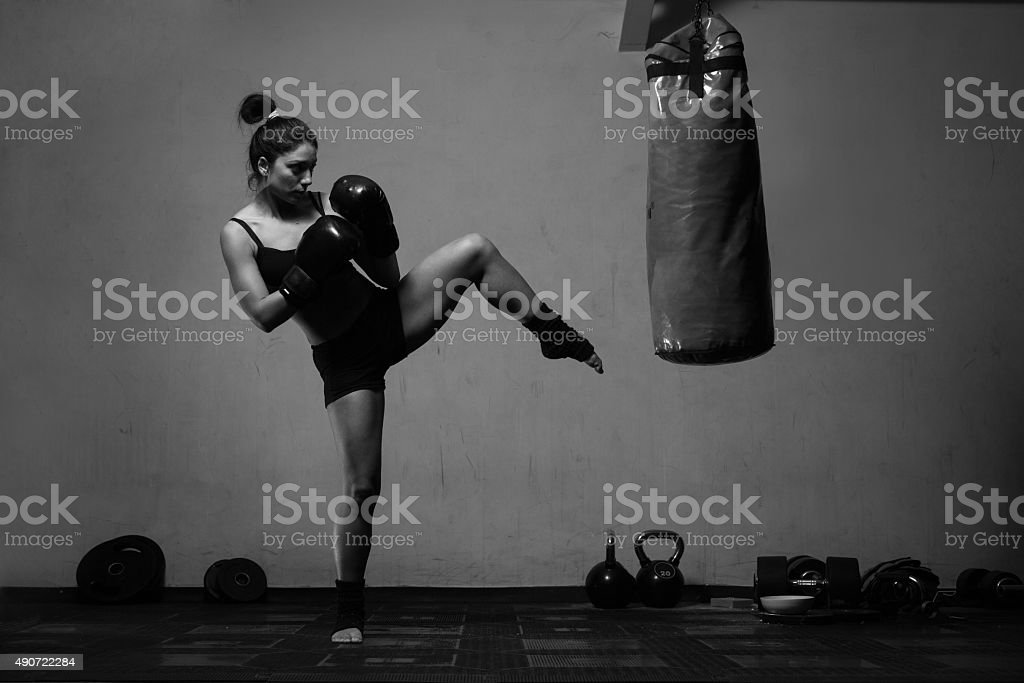 Young woman boxing workout in an old dark gym stock photo
