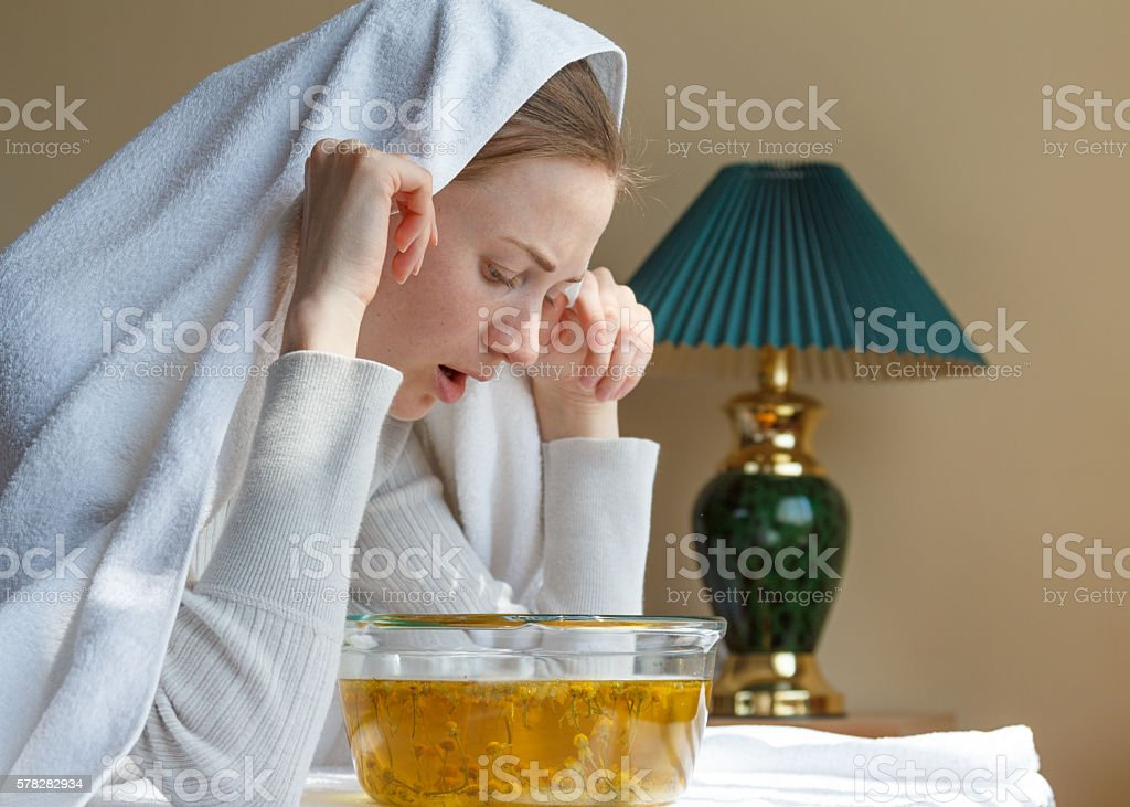young woman breathes herbal decoction stock photo