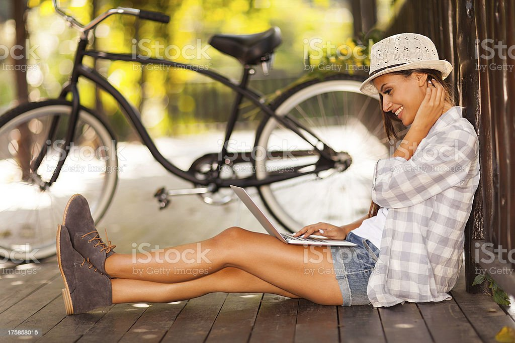 young woman browsing internet on her laptop outdoors stock photo