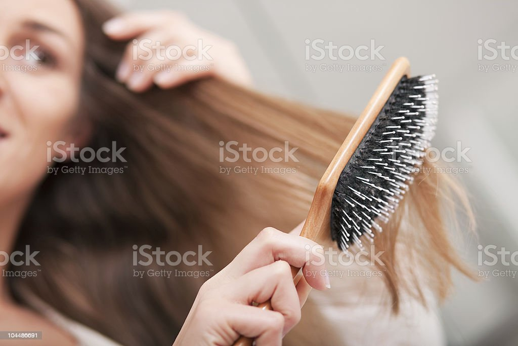 Young woman brushing her hair stock photo