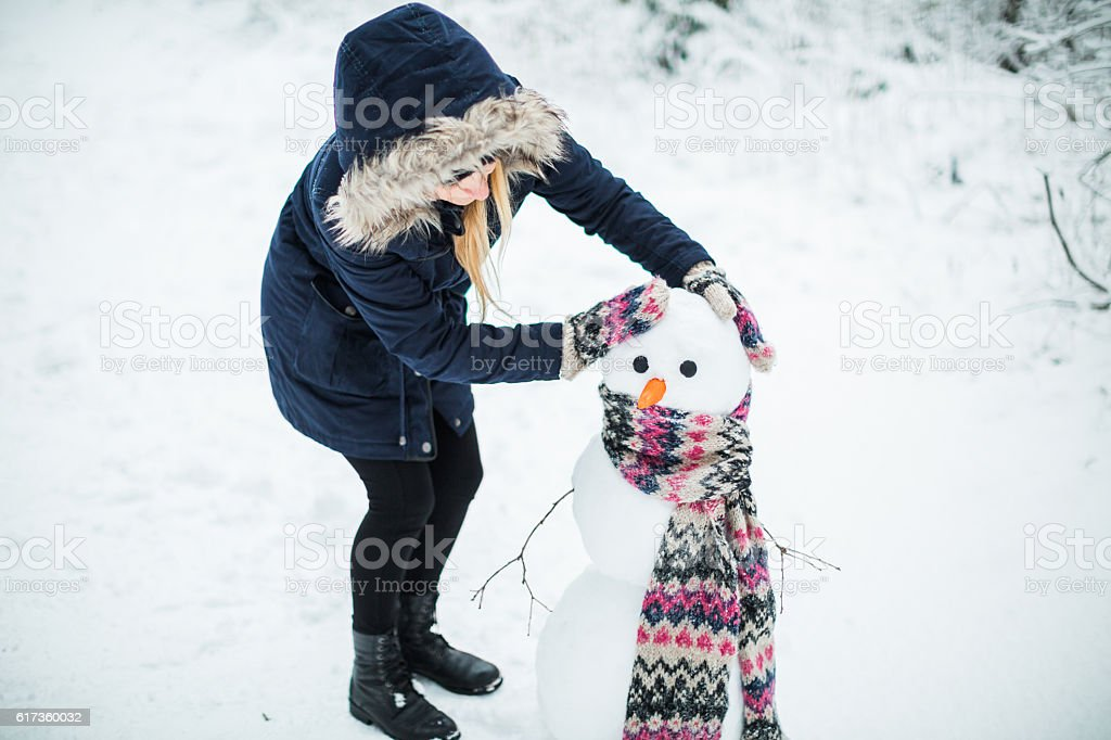 Young woman building snowman stock photo
