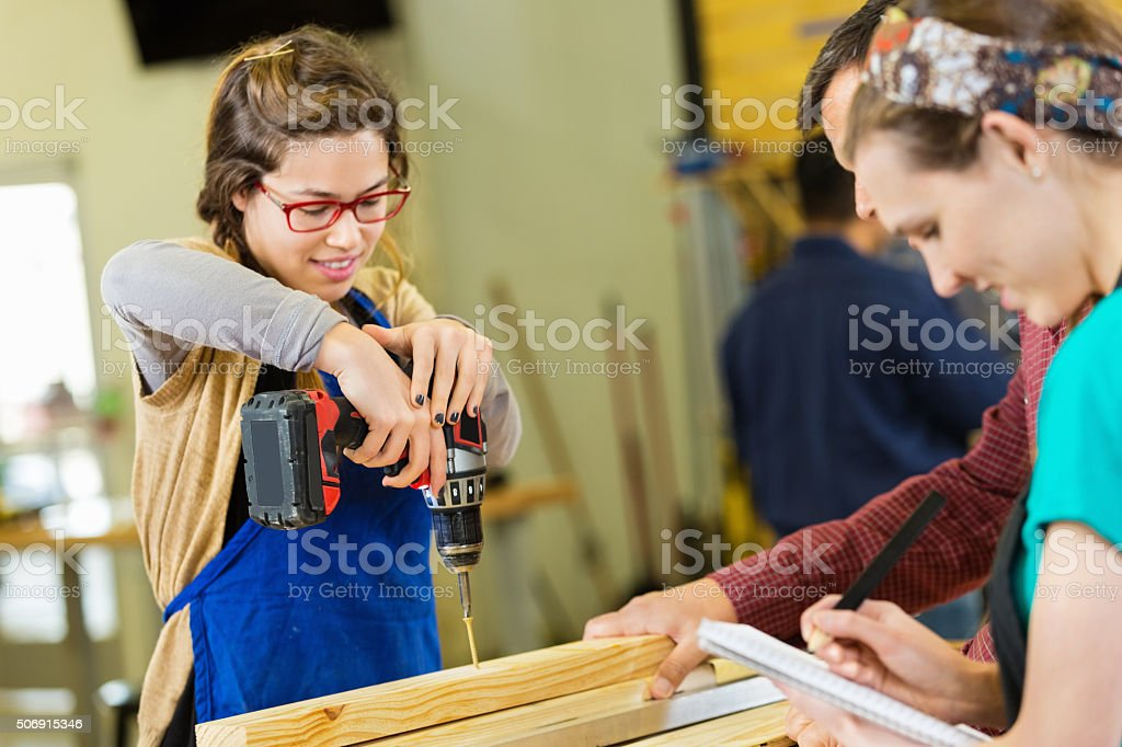 Young woman building something in workshop during wood working class stock photo