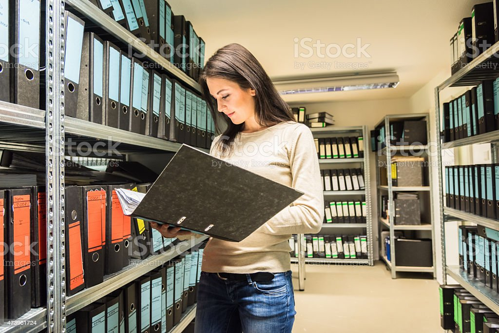 Young woman business accountant checking documents in finance file archive stock photo